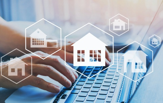 Hands typing at a laptop keyboard, with images of houses and properties, representing Property Management in Peoria IL