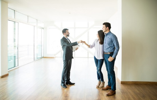 A real estate broker and couple coming to an agreement on Property Management in Peoria IL