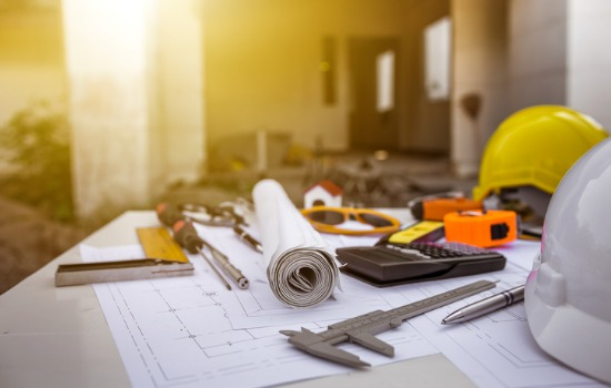 A blueprint and drafting tools on the site of a property development in Peoria IL